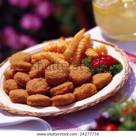 Chicken nuggets and french fries in outdoor setting.