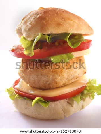 Chicken patties in homemade bread with cheese, onion, tomato and lettuce