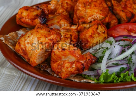 Chicken skewers bbq with tomato, bread, salad leaves and onion