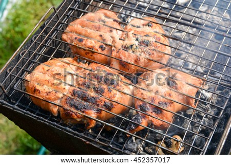 Chicken thighs in marinade, fried in a lattice on coals