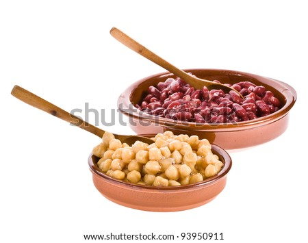 Chickpeas and red beans in bowls made ??of clay with a wooden spoon on white background