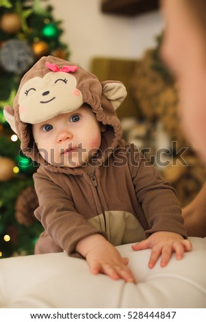 child dressed as a bear cub looking at the camera, the Christmas tree. Family values for Christmas. Parental care and love. Year of the monkey.