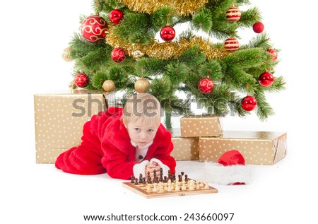 child dressed as a gnome play chess near a christmas tree and gift box.