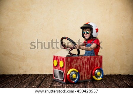 Child driving a car made of cardboard box. Kid having fun indoors. Child playing at home. Dream, imagination, childhood. Travel and summer vacation concept