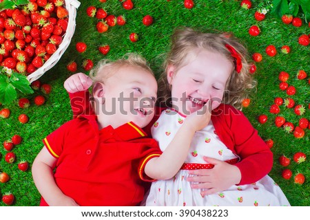 Child eating strawberry. Little girl and baby boy play and eat fresh ripe strawberries. Kids with fruit relaxing on a lawn. Children summer fun on a farm picking berry.