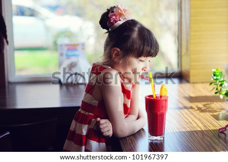 Child girl drinking strawberry smoothie sitting at a table in restaurant