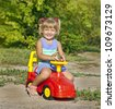 child girl driving her red toy vehicle in the park, outdoors - stock photo