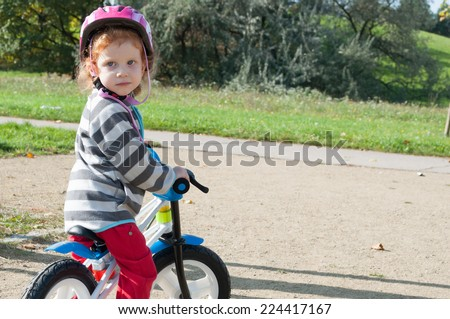 Child girl with the safety helmet on the bike in the autumn park