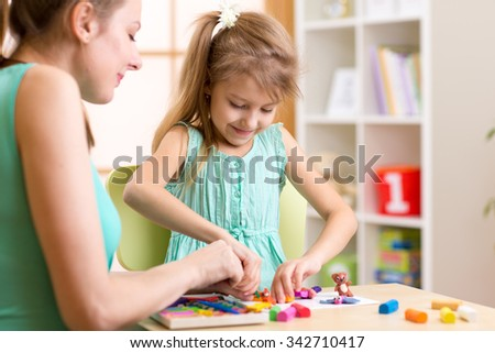 child kid girl and woman play colorful clay toy at nursery or kindergarten