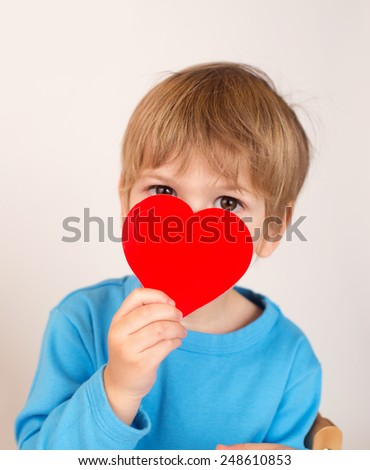 Child, kid, holding up a valentine's day paper heart,