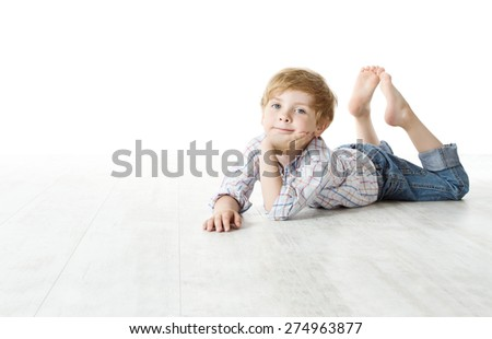 Child lying down on floor, Kid Boy over white background, looking at camera