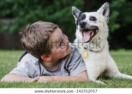 Child playing with his pet dog, a blue heeler