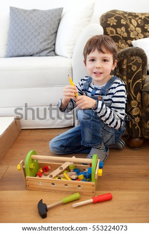Child playing with toy toolbox at home