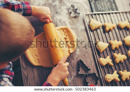 Child rolling out dough for christmas cookies