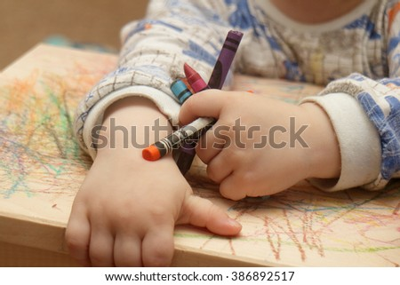 Child's hands holds pencils.Closeup.