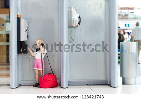 child with bag talking the phone in the airport