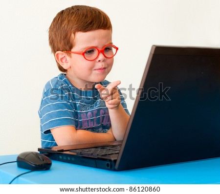 Child with glasses pointing on computer