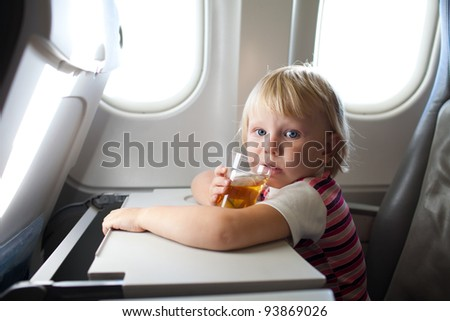 child with juice in airplane