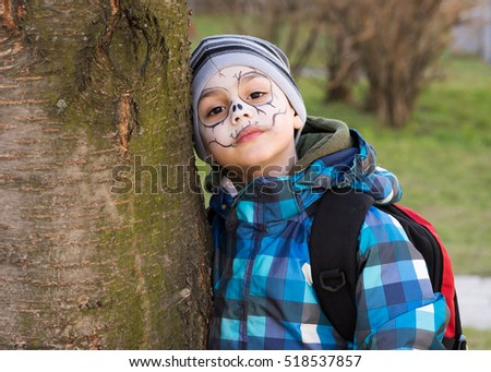 Child with scary face painting  leaning against a tree