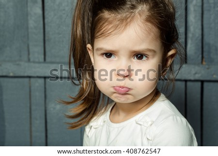 Childhood and emotions. Little girl with funny face closeup.