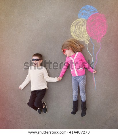 Children are holding hands outside with colorful chalk balloons sketched out on cement for a creative, craft or play concept.