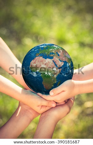 Children holding blue planet in hands against green spring background. Earth day holiday concept. Elements of this image furnished by NASA