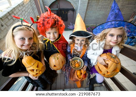 children in halloween costumes with pumpkin walk in guests