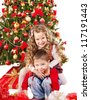 Children in Santa hat with gift box near Christmas tree. Isolated. - stock photo