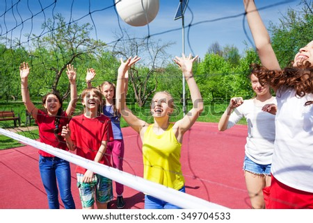 Children play actively near the volleyball net on the court during sunny summer day outside