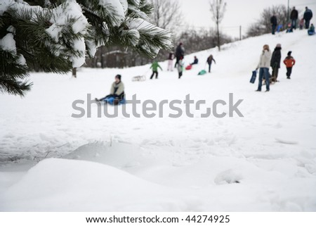Children playing in winter - sledging on a hill