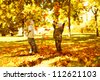 Children playing with autumn fallen leaves in park - stock photo