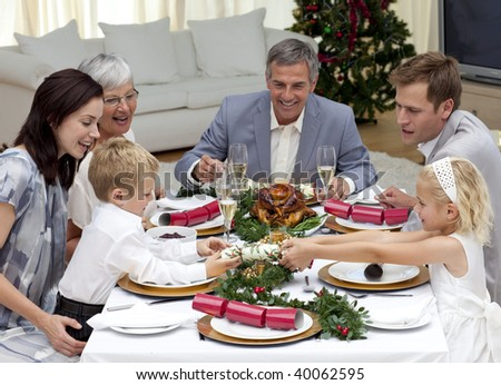 Children Pulling A Christmas Cracker At Home In Family Dinner