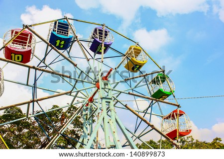 Children's carousel with colored booths against the blue sky