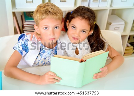 Children sit at the table with books and looking into the camera. Educational concept.
