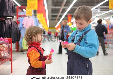 Children with sweetmeats in supermarket, focus on little girl