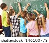 Children writing on blackboard at school. - stock photo