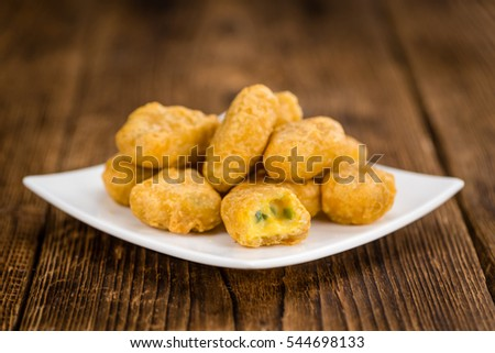 Chili Cheese Nuggets on a vintage background as detailed close-up shot (selective focus)