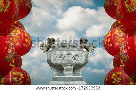 Chinese lanterns and incense stick pot against cloudy blue sky, chinese new year