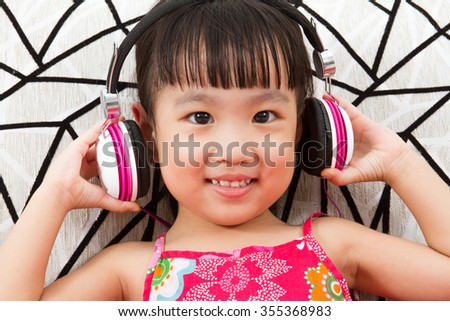Chinese little girl on headphones holding mobile phone sitting on sofa