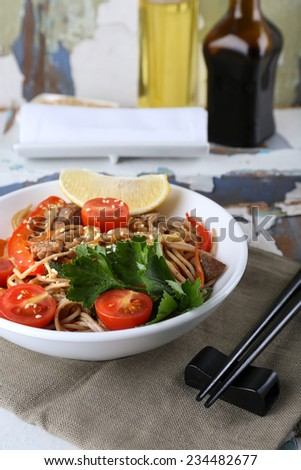 Chinese noodles with vegetables and roasted meat in bowl on napkin, on wooden background