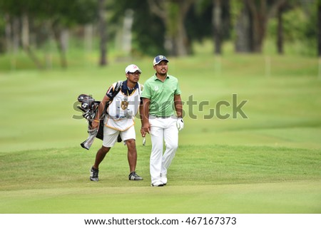 Chinnarat Phadungsil of Thailand with caddy in action during round four of the King's Cup at Phoenix Gold Golf and Country Club on July 31, 2016 in Pattaya, Thailand.
