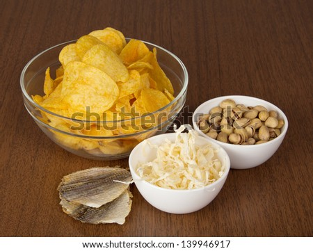 Chips, pistachios, dried squids and salty fish, on a table