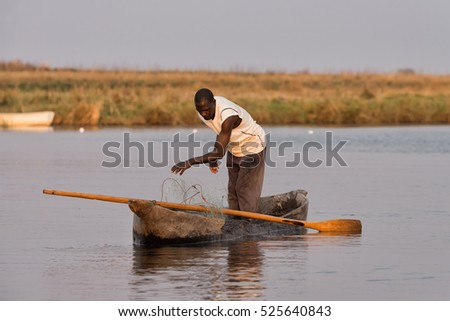 CHOBE RIVER, NAMIBIA - SEPTEMBER 11, 2016: Man fish with nets from his dugout canoe at sunset in the Chobe River between Namibia and Botswana.