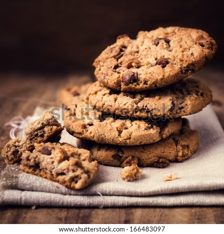 Chocolate cookies on white linen napkin on wooden table. Chocolate chip cookies in rustic style close up.