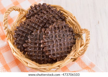 Chocolate covered round homemade cookies in wooden basket