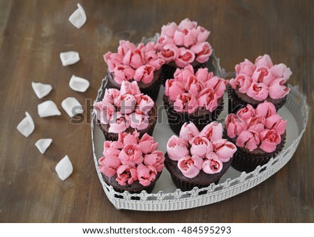 Chocolate cupcakes with pink vanilla buttercream rosebuds in a heart shaped platter