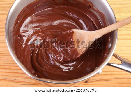 chocolate ganache in the saucepan on wooden table
