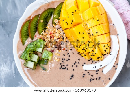 Chocolate smoothie bowl with kiwi, mango and granola. Love for a healthy raw food concept.