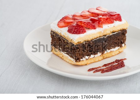Chocolate strawberry cake on white plate and wooden table.