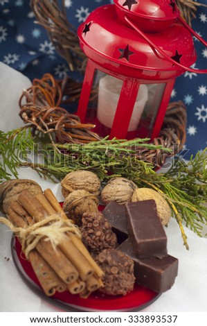 chocolates, cinnamon and walnuts on a background of a New Year composition